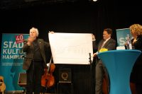 Werner Frömming übergibt das Geschenk der Behörde für Kultur und Medien ...